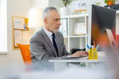 Serious smart office worker dealing with his duties. Data on the screen. Serious smart office worker dealing with his duties while sitting in front of spacious royalty free stock photography
