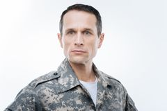 Serious smart serviceman thinking about his country. True patriot. Serious nice smart serviceman standing against white background and thinking about his country Royalty Free Stock Image
