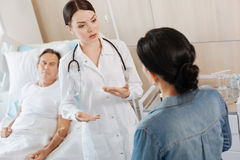 Serious smart therapist talking to her patients wife stock image