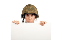 Serious soldier girl. Holding advertising space on white background royalty free stock photography