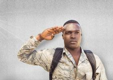 Serious soldier saluting. Concrete wall Stock Image