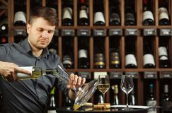 Serious sommelier pouring white wine in decanter. Serious sommelier pouring white wine from opened bottle in decanter designed to degustate and taste alcohol Stock Images