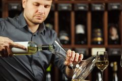 Portrait of serious sommelier pouring white wine in decanter. Serious sommelier pouring white wine from opened bottle in decanter to degustate and taste alcohol stock photos