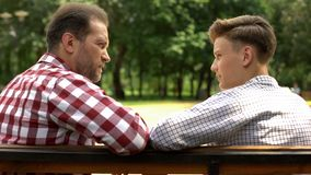 Serious son and dad talking on bench in park, father sharing life experience. Stock photo stock image