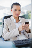Serious sophisticated businesswoman texting Royalty Free Stock Photography
