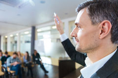 Serious speaker standing with raised hand on business meeting Royalty Free Stock Images