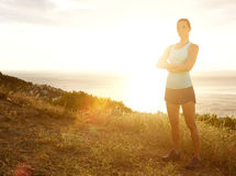 Serious sport woman with arms crossed standing in sunset Stock Photo