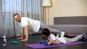 Serious sportive family doing plank exercise with dumbbells at home, role model. Stock photo stock images