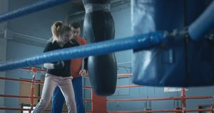 Girl boxing punchbag with trainer. Serious sportive girl punching bag while training with boxing coach on ring stock video footage