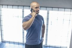 A serious sports coach speaks by telephone with a client in a gym. dressed in a sports uniform royalty free stock photos