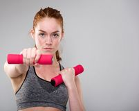 Serious sports woman holding weights Royalty Free Stock Image