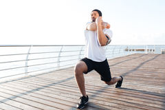 Serious sportsman stretching legs and arms at the sunrise. Serious african american young sportsman stretching legs and arms at the sunrise Stock Images