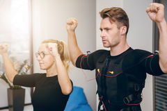 Serious sportsman working out with personal coach at gym. Side portrait of serious sportsman working out with personal coach at gym Royalty Free Stock Photo
