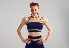 Serious sportswoman in blue sportswear. Posing in studio Royalty Free Stock Image