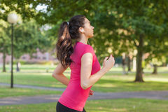 Serious sporty woman jogging in a park Stock Image