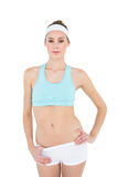 Serious sporty woman posing with hand on hips looking at camera Royalty Free Stock Photo