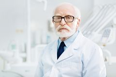 Serious stomatologist standing in dental cabinet Stock Photos