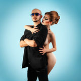 Serious strong man with hot naked woman in studio Royalty Free Stock Photos