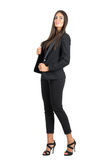 Serious strong business woman in black suit posing at camera. Royalty Free Stock Images