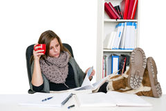 Serious student. Young female student, diligently reading her notes whilst studying with her feet on the desk and a cup in her hand, looking serious Stock Photos