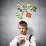 Serious student with arms touching his chin. And thinking about something. Redhead boy with drawing ideas tree above head. Clever guy wears white shirt and stock image