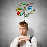 Serious student with arms touching his chin. And thinking about something. Redhead boy with drawing ideas tree above head. Clever guy wears white shirt and stock photo