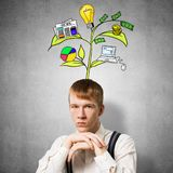 Serious student with arms touching his chin. And thinking about something. Redhead boy with drawing ideas tree above head. Clever guy wears white shirt and royalty free stock images
