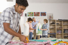 Serious student cutting fabric in home economics classroom Stock Images
