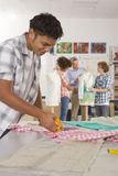 Serious student cutting fabric in home economics classroom Royalty Free Stock Photos
