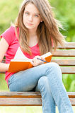 Serious student girl sitting on bench with book Stock Photos