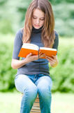 Serious student girl sitting on pile of books Stock Photography