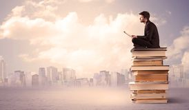Businessman with laptop sitting on books Royalty Free Stock Photography