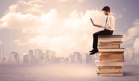 Businessman with laptop sitting on books. A serious student with laptop tablet in elegant suit sitting on a stack of books in front of cityscape with clouds Stock Photo