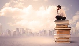 Businessman with laptop sitting on books Royalty Free Stock Photo