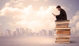 Businessman with laptop sitting on books. A serious student with laptop tablet in elegant suit sitting on a stack of books in front of cityscape with clouds Royalty Free Stock Images