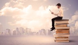 Businessman with laptop sitting on books. A serious student with laptop tablet in elegant suit sitting on a stack of books in front of cityscape with clouds Stock Photography