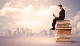 Businessman with laptop sitting on books. A serious student with laptop tablet in elegant suit sitting on a stack of books in front of cityscape with clouds Royalty Free Stock Photo
