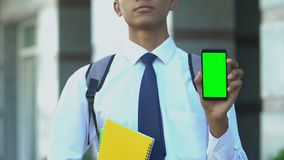 Serious student showing cell phone, apps for enrollment in specialized school. Stock footage stock footage