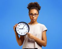 Serious student shows clock, demonstrates its time to work!. Photo of african american girl wears casual outfit on blue background. Emotions and pleasant royalty free stock images