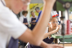 Serious student using drill in vocational school stock images