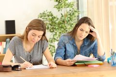 Serious students doing homework at home royalty free stock image