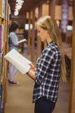 Serious students reading next to bookshelf Stock Photo