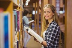 Serious students reading next to bookshelf Stock Photography