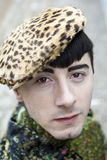 Serious style young man looking at camera. Young male model in leopard cap Stock Photo