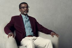 Serious stylish african american man. Sitting in armchair royalty free stock photo