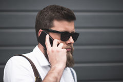 Serious stylish bearded man in sunglasses using smartphone Stock Photo