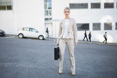 Serious stylish businesswoman holding briefcase posing Stock Photography