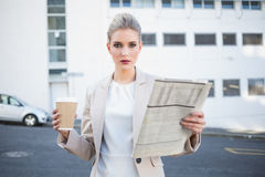 Serious stylish businesswoman holding newspaper and coffee Stock Images