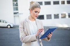 Serious stylish businesswoman scrolling on digital tablet Royalty Free Stock Photos