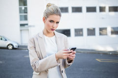 Serious stylish businesswoman sending a text Royalty Free Stock Photos